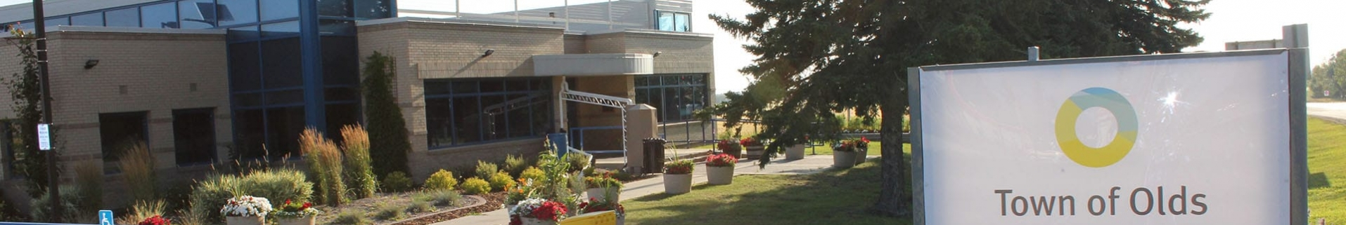 """Sign that says """"Town of Olds"""" outside a concrete building"""