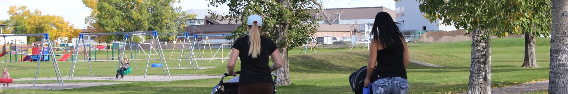 Two young women pushing strollers through a park in the summer time