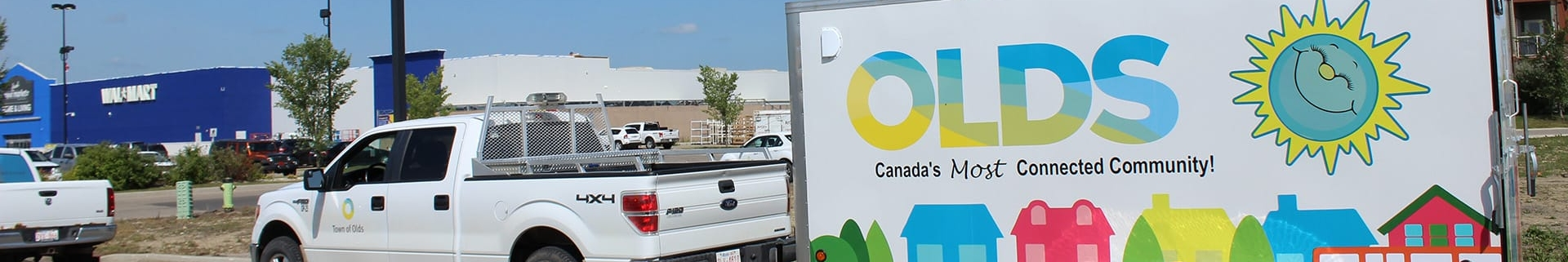 """White pick up truck with the Town of Olds municipal logo with a colourful trailer hitched to the back, reading """"Olds - Canada's most connected community!"""""""