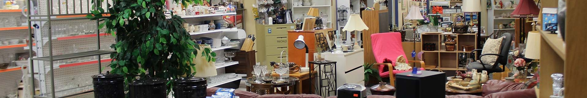 Thrift store setting with many household items and furniture placed throughout the store