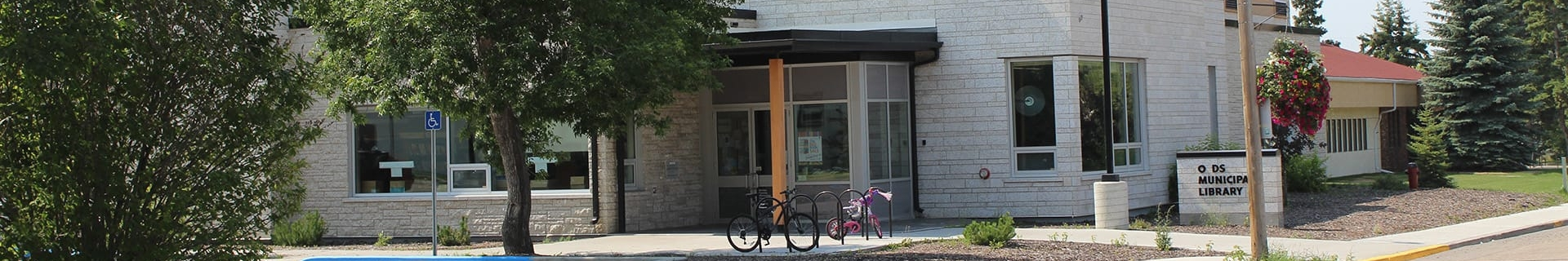 "Brick building with bicycles parked in front and a sign that reads ""Olds Municipal Library"""