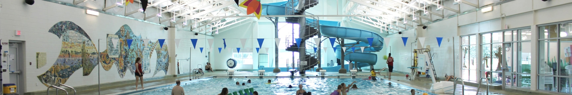 Children and adults swimming in view of the swimming pool and waterslide at the Olds Aquatic Centre
