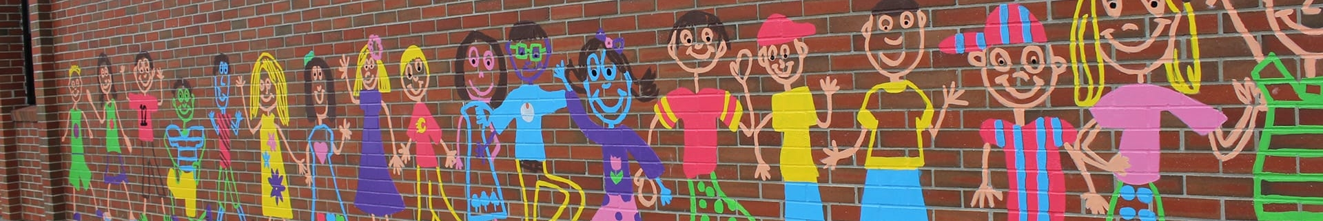 Brick wall with colourful paintings of schoolchildren smiling and waving