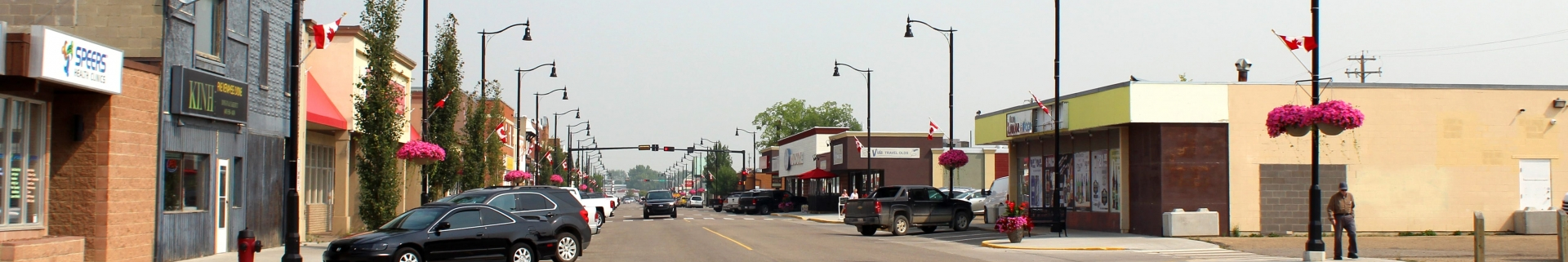 Cars parked and driving down the Main Street of the Town of Olds