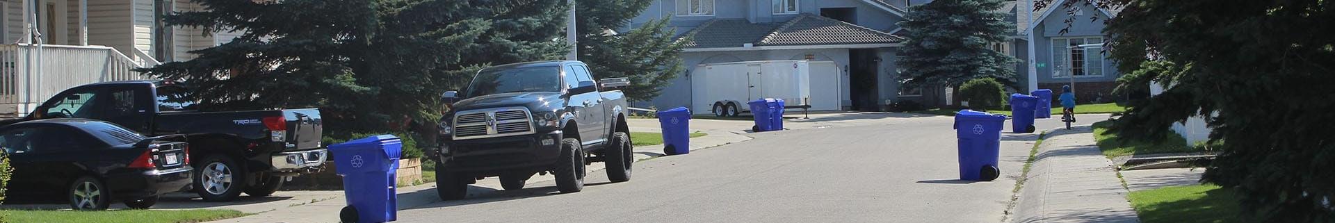 Residential street with a black pick-up truck parked and blue waste bins on the curb