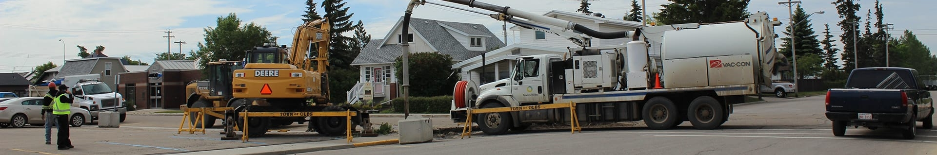 Large trucks on a residential street with a construction zone blocked off